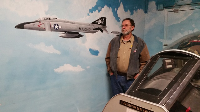 Dean standing in front of the wall mural depicting the F-4 Phantom, which he worked on as an aircraft electrician when he was in the U.S. Marine Corps